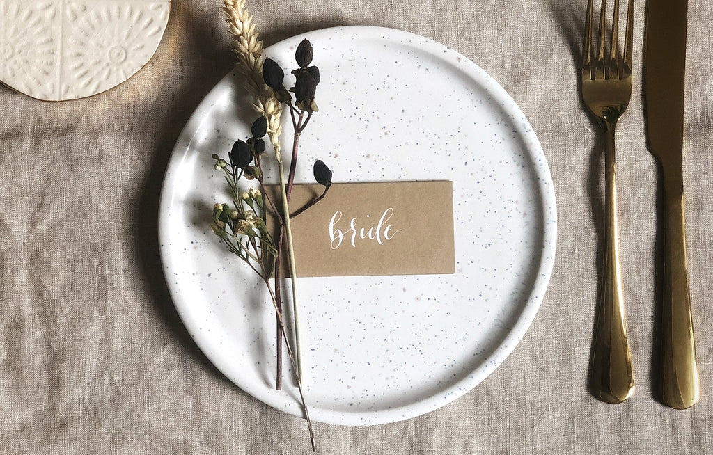 natural coloured wedding place cards with white calligraphy