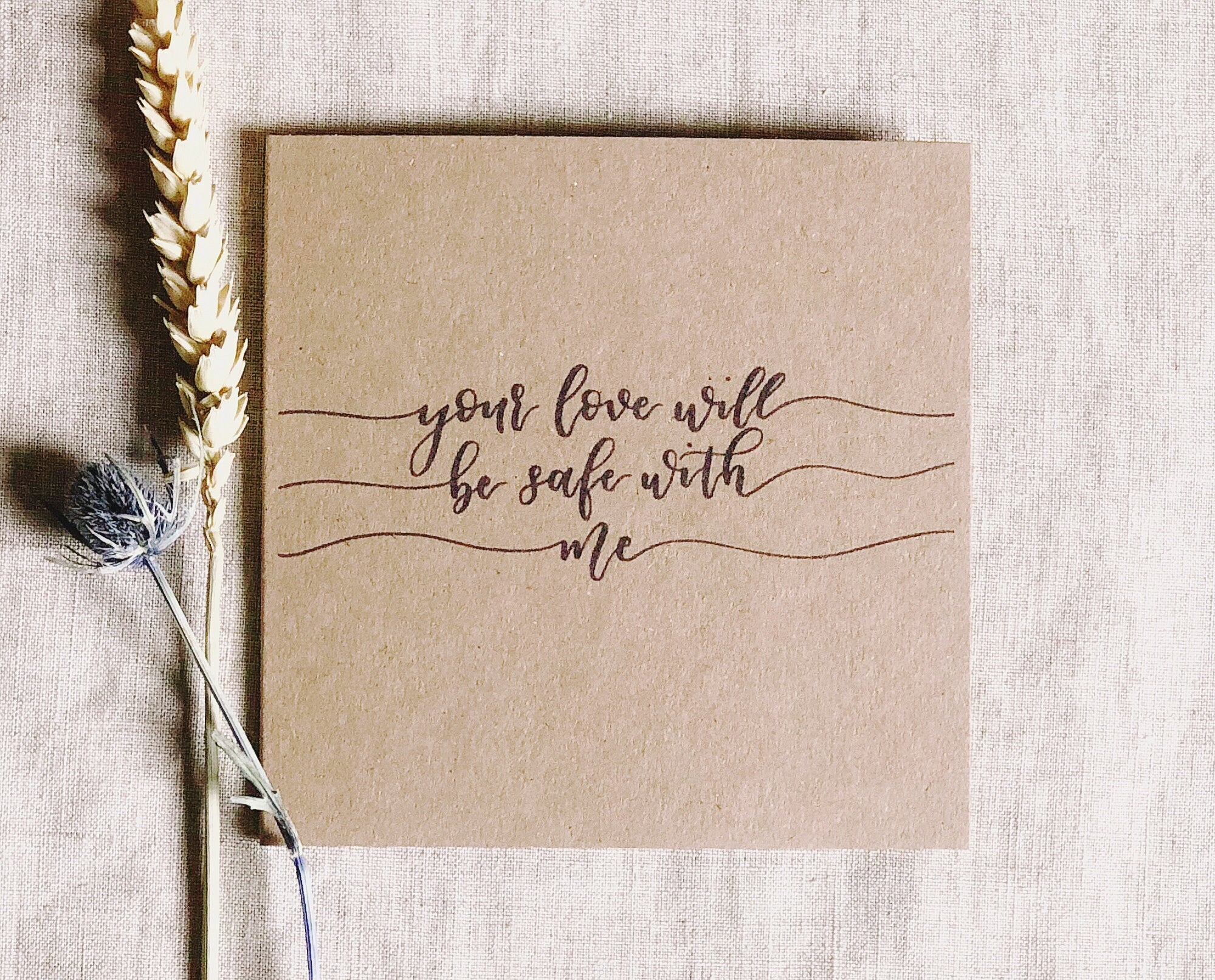 kraft brown card with lyrics written in modern black calligraphy