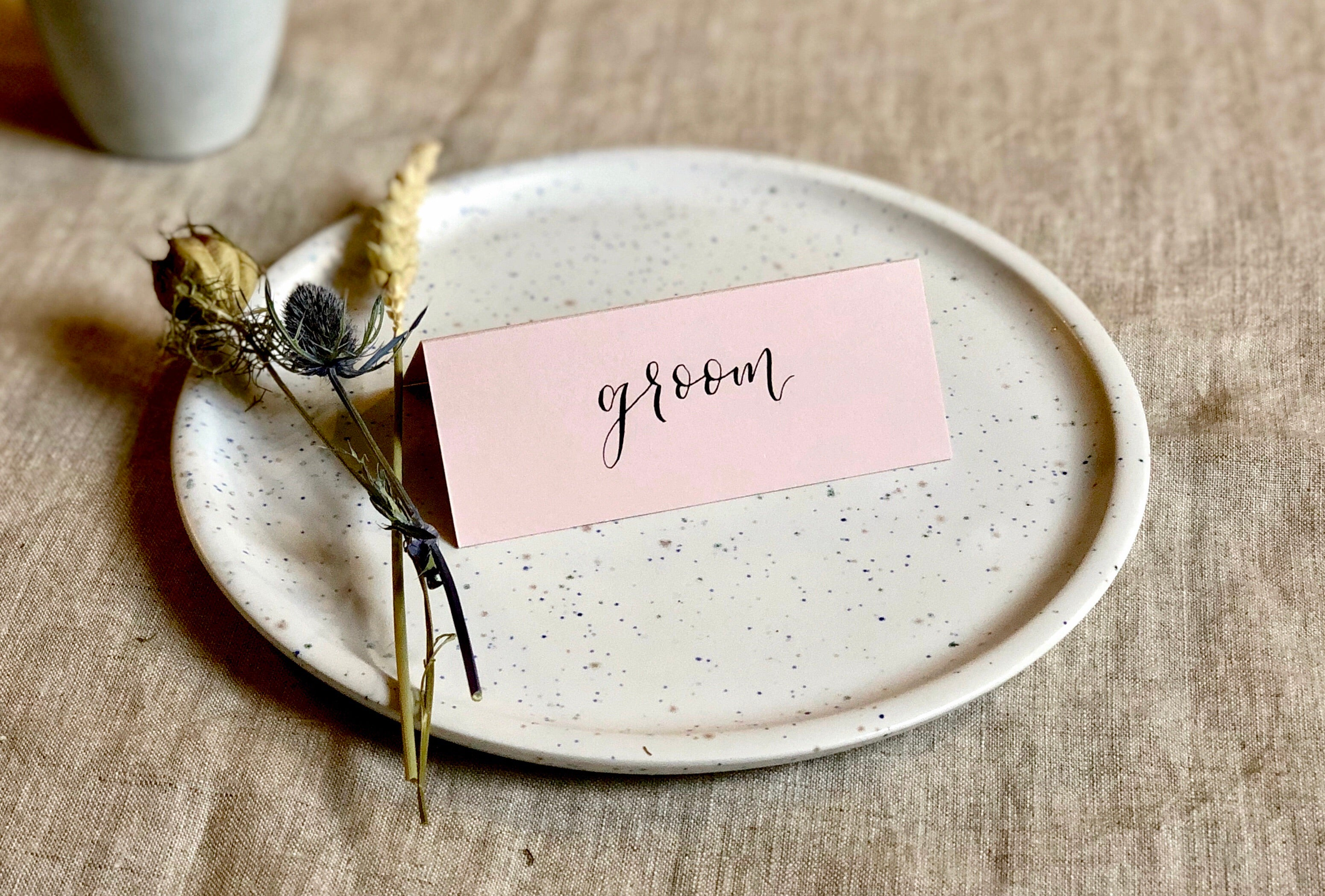 dusty pink wedding place card with black calligraphy
