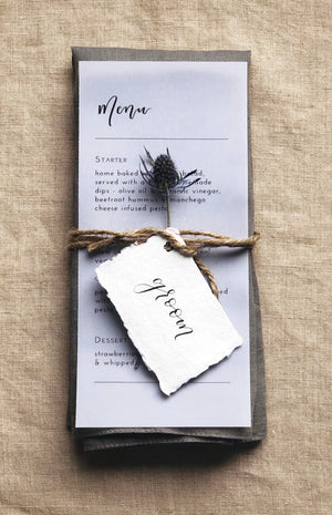 vellum paper menu with black text, napkin, white cotton name cards with calligraphy and flower table decor idea 2