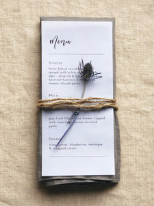 vellum paper menu with black text, napkin and flower table decor idea