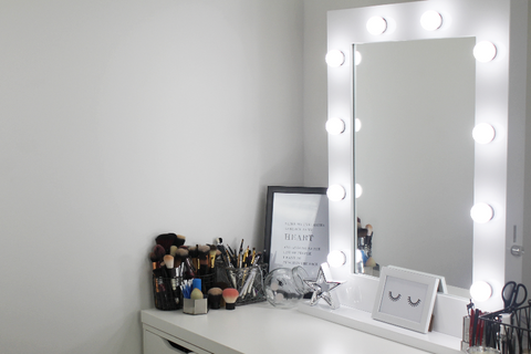 white gloss hollywood mirror with lightbulbs switched on