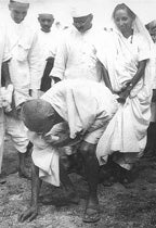 Salt March led by mahatma ghandi, ghandhi is picking up grains of salt at the end of march to protest taxation by british. part of peaceful resistance movement leading to indendence india 1947.