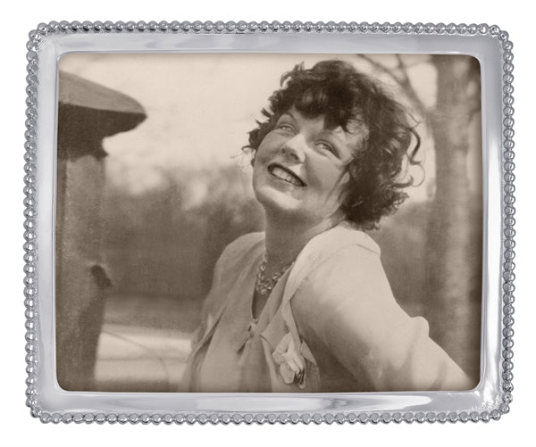 A silver frame with a thin frame and small silver beading around the edge. A  black and white stock photo of a woman with short hair smiling sits within the frame.