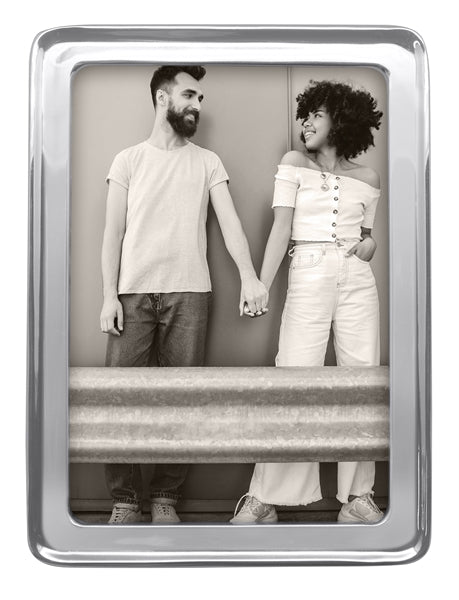 "A silver 5"" by 7"" frame with a stock photo of a modern day couple holding hands by a guard rail."