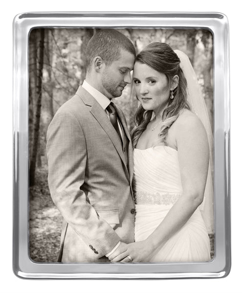 "A 8"" by 10"" silver photo frame with a stock photo of a couple on their wedding day."
