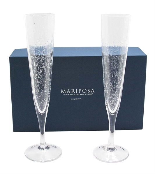 Two champagne flutes in front of a navy blue Mariposa gift box.