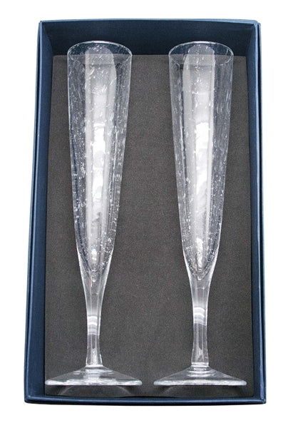 Two champagne flutes laying in navy blue Mariposa gift box.