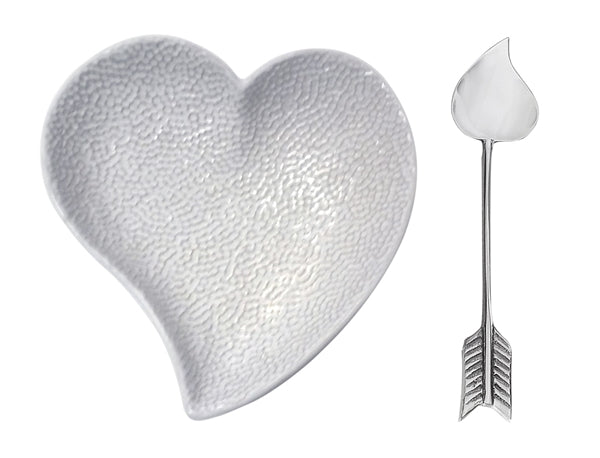 A white ceramic heart dish with an heart topped arrow spoon.