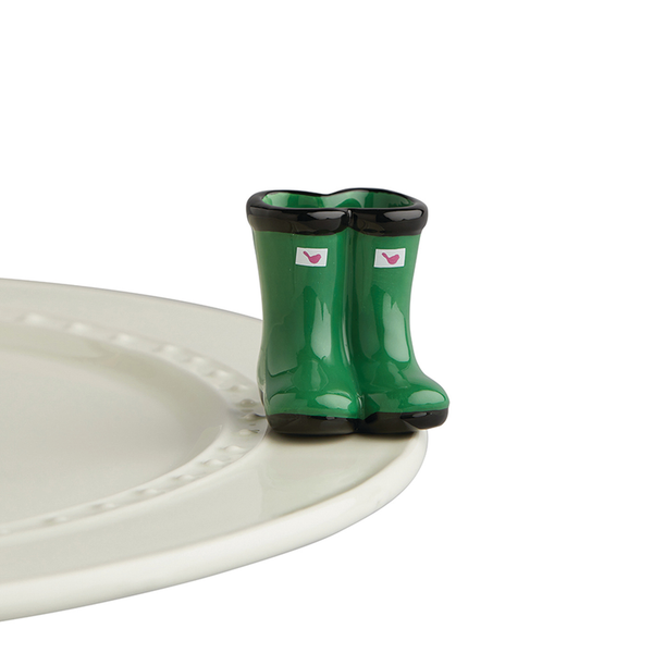 Porcelain hunter green galoshes with a pink Nora Fleming logo on the top front.