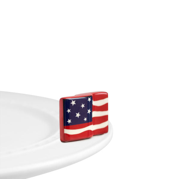 A porcelain waving American flag ornament a top a Nora Fleming dish.