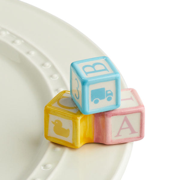A porcelain trio of pastel blue, pink and yellow baby blocks sitting a top a Nora Fleming dish.