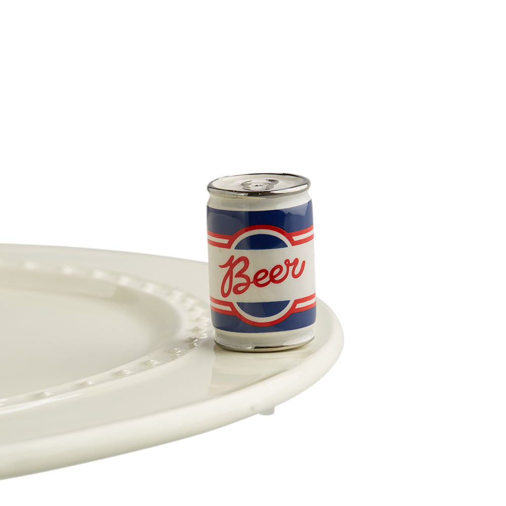A porcelain red, blue and white beer can with beer written in center on top of Nora Fleming dish.