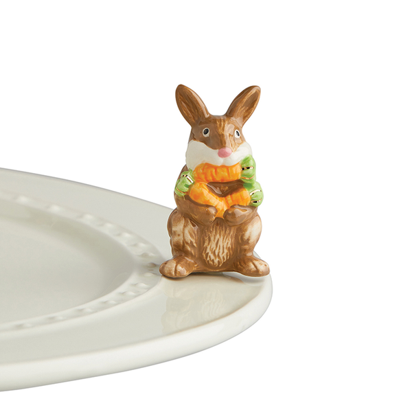A porcelain bunny holding three carrots.