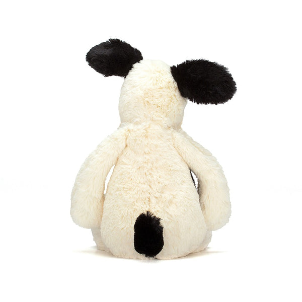 The back of a cream colored puppy with black tail and ears sitting on a white background