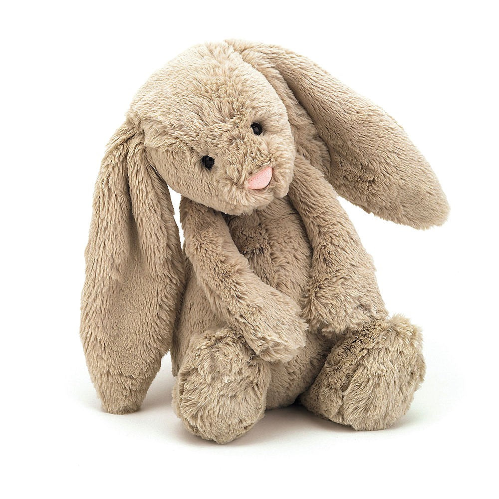 A beige plush bunny with his head tilted slightly on a white background.