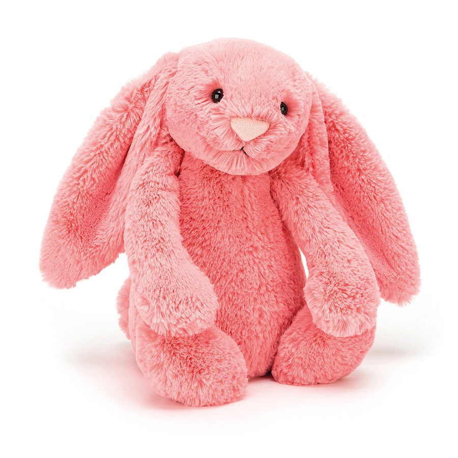 A vibrant pink plush bunny sitting on a white background.