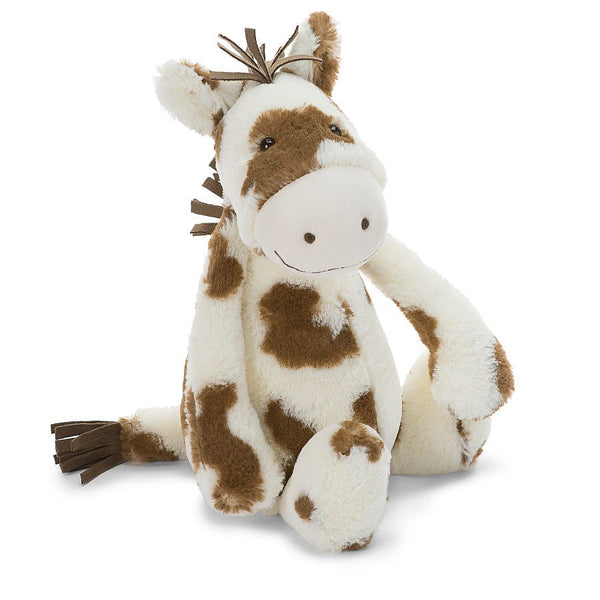 A plush pinto pony with brown spots, mane and tail sitting on a white background.