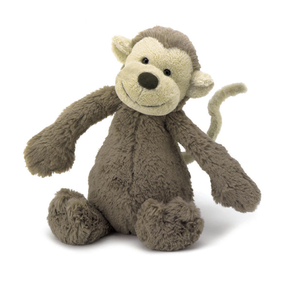 A deep brown plush monkey sitting happily on a white background.