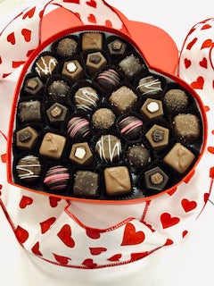 A large red heart shaped box filled with assorted chocolates.