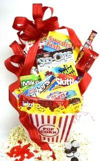 A red striped popcorn bucket overflowing with theater candy and popcorn with a big red ribbon.