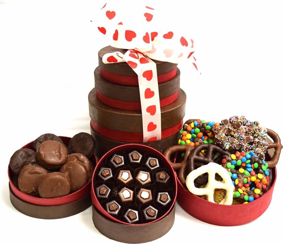 A gift tower overflowing with chocolates and stacked high with a heart printed ribbon.