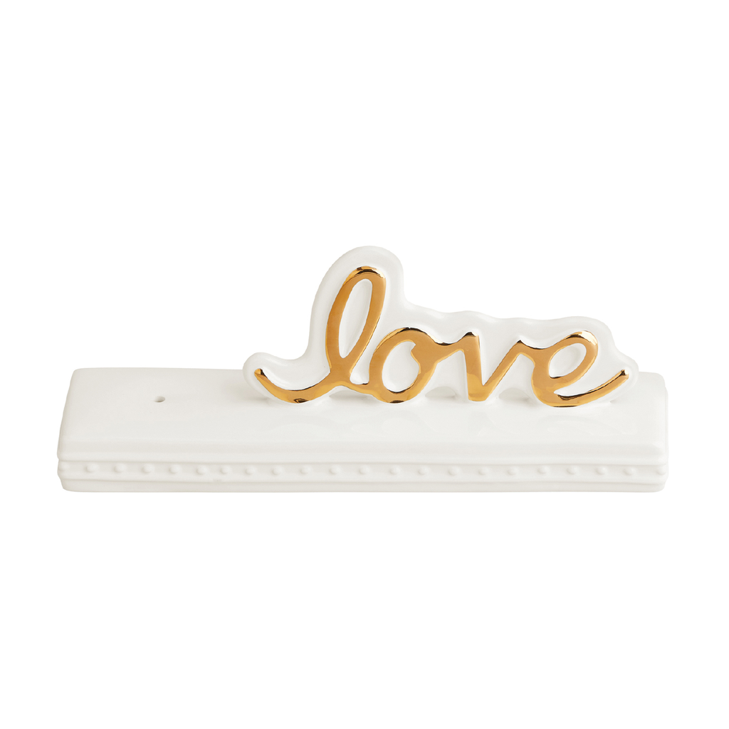 A ceramic plaque with cursive gold love to the right.