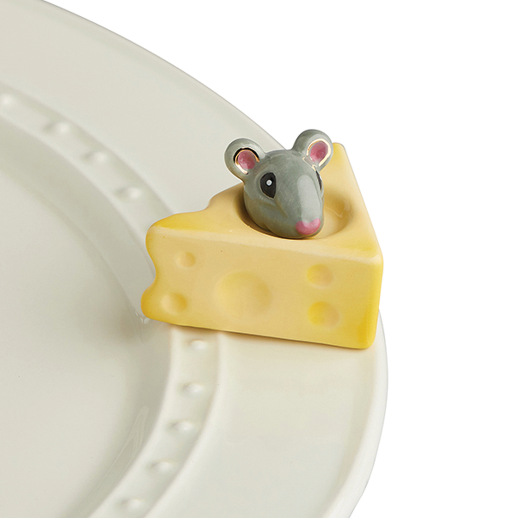 A porcelain wedge of cheese with a mouse peeking out of the top.