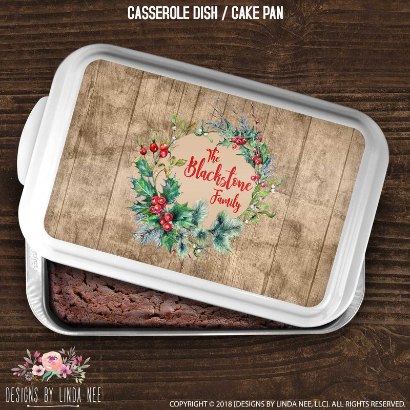 Covered pan featuring rustic wood panel with red berries on wreath surrrounding family name