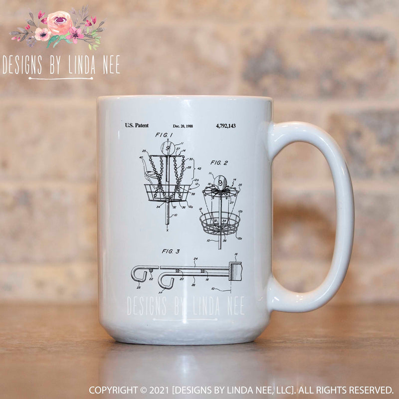 White mug featuring a disc golf patent sketch of basket front and side view with detail of bracket