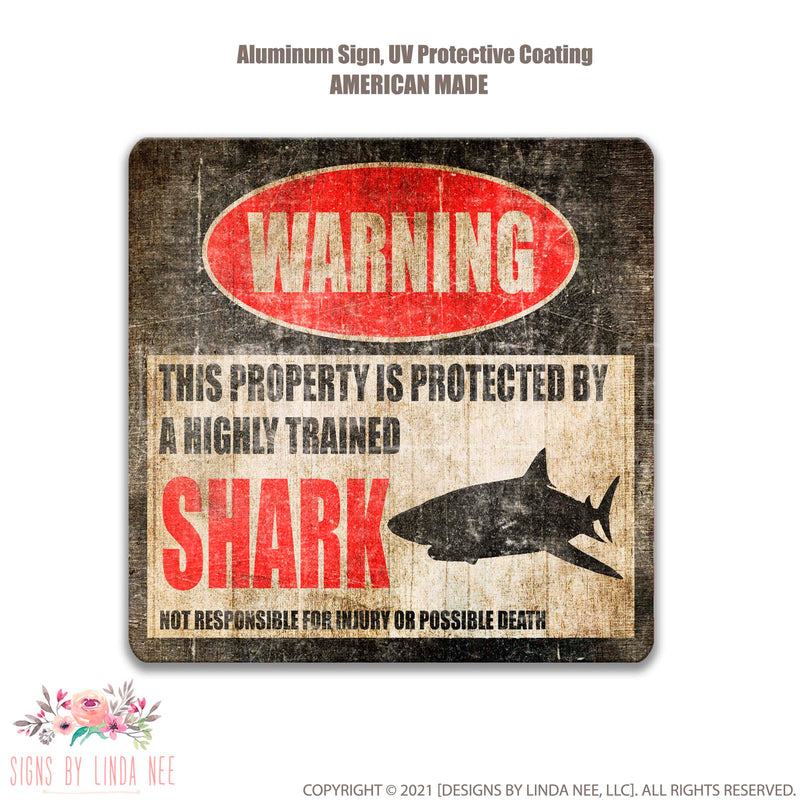 Distressed background with font saying Warning This Property is Protected by a Highly trained Shark Not responsible for injury or possible death Sign
