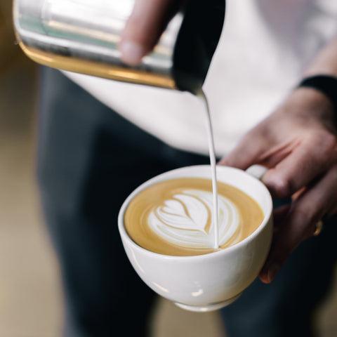 Barista pouring latte art into a cup with a steel pitcher