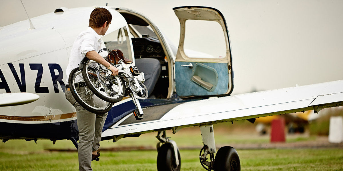 Man with folded Bickerton foldable bike putting it on a small airplane