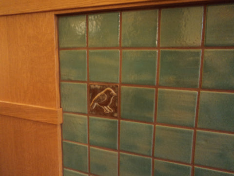 handmade chickadee tile installed in fireplace hearth