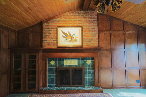 wood paneled library with green art tile fireplace surround
