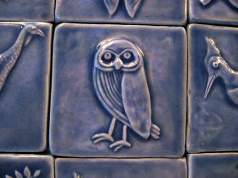 handmade owl tile in blue glaze surround by other handmade tiles