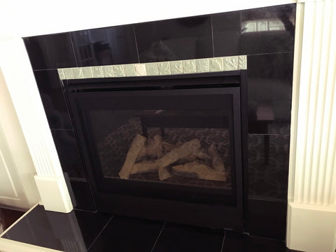 small light colored handmade tiles depicting plants installed with black stone tiles in a fireplace surround