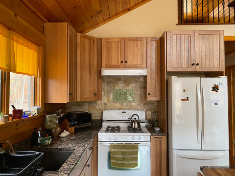 the kitchen of a log cabin featuring handmade tiles over the stove