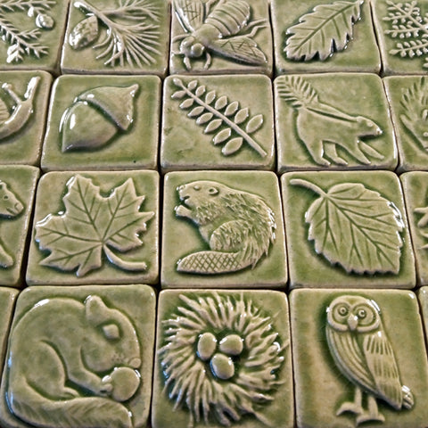 two inch by two inch handmade tiles featuring plants and animals in a light green glaze