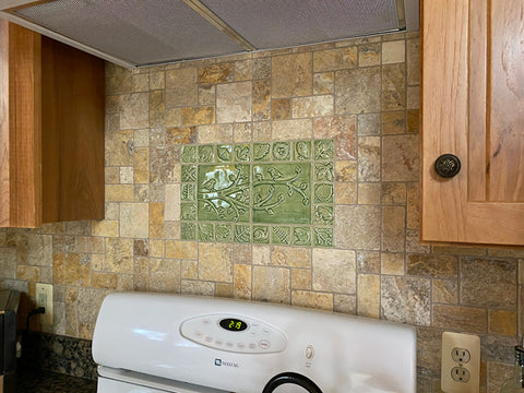 handmade tiles set over the stove in a log cabin kitchen