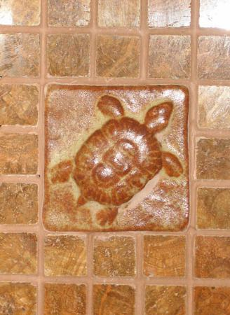 Fireplace surround with hand-made ceramic turtle tile