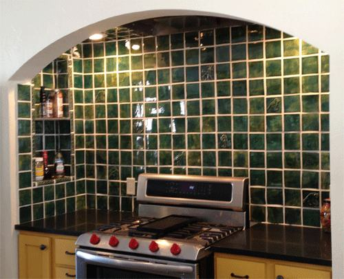 leaf green art tiles in a kitchen with yellow cupbaords