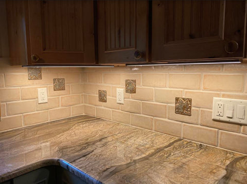 handmade maple leaf tiles installed in a kitchen backsplash