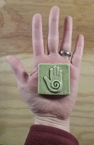 light green two inch by two inch healing hand handmade tile in the palm of a hand