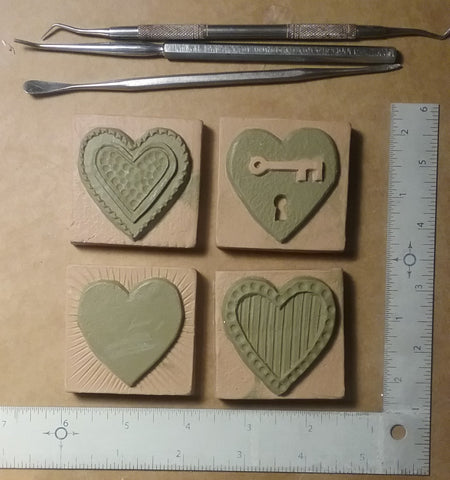sculpting handmade tiles with heart designs, two inch by two inch size