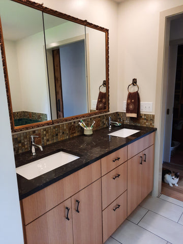 handmade tiles installed over a double sink in a bathroom