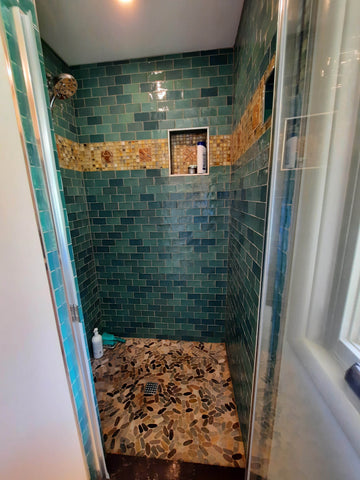 handmade tiles installed in a shower along with green subway tiles
