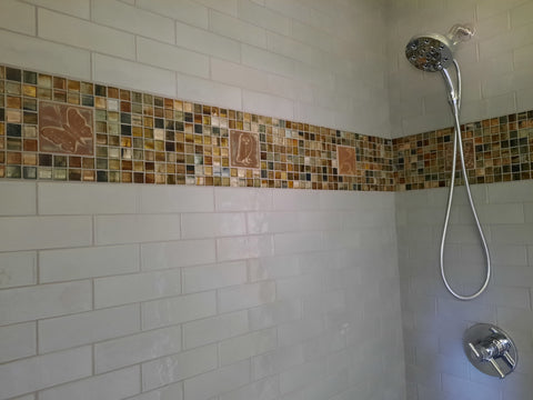 tiled shower with a stripe of handmade tiles mixed with glass tiles
