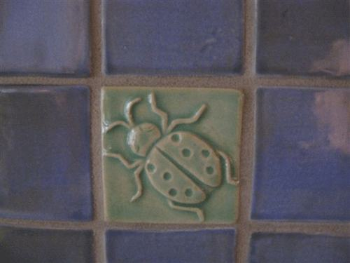 ladybug art tile installed with handmade field tiles