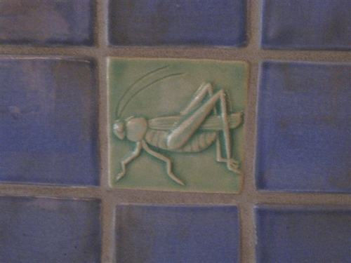 grasshopper art tile installed with handmade field tiles